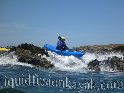 Sit on top kayak kayaks over the rocks on a wave while rock garden kayaking on the Mendocino Coast.